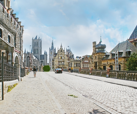 The St Michaels street leads to the main city landmarks along the  the same named bridge and Sint-Michielskerk, stepped gable mansions and across Leie river, Ghent, Belgium.