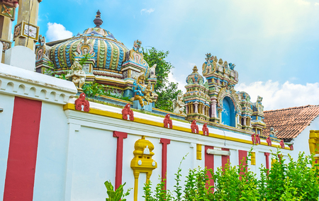dome of hindu temple: The dome and gate decorations of Munneswaram Kovil consist of colorful sculptures and carved patterns, located behind the outer striped wall, Munneswaram village, Sri Lanka. Editorial