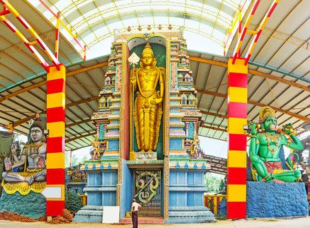 The facade statues in Murugan Kovil in Chilaw - the golden Skanda (Murugan) in the middle, sitting God Shiva and Hanuman, Sri Lanka. Editorial