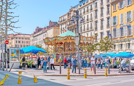 MARSEILLE, FRANCE - MAY 4, 2013: The old fashioned carousel surrounded by flower market stalls in crowded General de Gaulle Square, on May 4 in Marseille. Publikacyjne