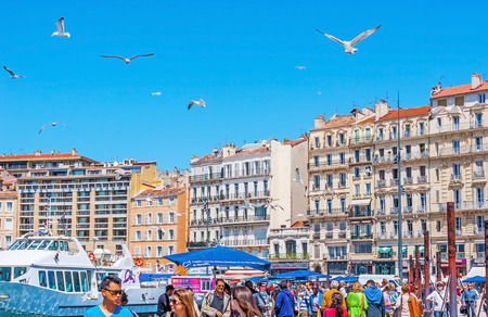 MARSEILLE, FRANCE - MAY 4, 2013: The seagulls fly over the crowded fish market and Vieux Port, on May 4 in Marseille. Editorial