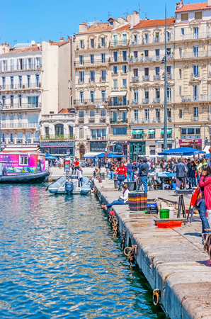 MARSEILLE, FRANCE - MAY 4, 2013: The quay of Vieux Port is the crowded place, tourists walk here, searching for attractions, views, cafes and bars, locals visit fish market or go to the shipyards, on May 4 in Marseille.