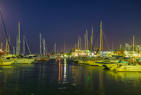 EL KANTAOUI, TUNISIA - AUGUST 28, 2015: The rows of white yachts rock on the gentle waves in port, on August 28 in El Kantaoui.