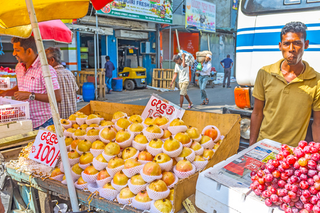 COLOMBO, SRI LANKA - DECEMBER 6, 2016: The yellow pomegranates and grape on the old carts of street market in Pettah, on December 6 in Colombo.