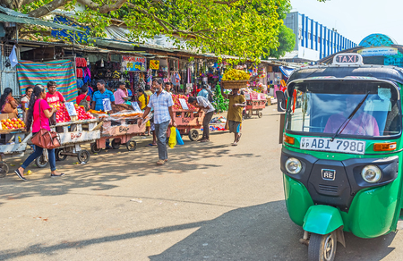 COLOMBO, SRI LANKA - DECEMBER 6, 2016: The small tuk-tuk taxis are very popular in such areas as crowded Pettah Market with its narrow rows and streets, occupied with shops, stalls and spontaneous trade, on December 6 in Colombo. Editorial