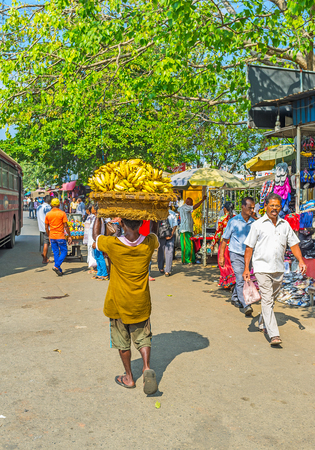 COLOMBO, SRI LANKA - DECEMBER 6, 2016: The porter at Pettah Market carries the basket with bananas on his head, on December 6 in Colombo.