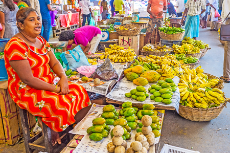 COLOMBO, SRI LANKA - DECEMBER 6, 2016: The fruit seller at Fose Market in Pettah, repeats the prices of bananas, papayas and wooden apple fruits to attract the clients, on December 6 in Colombo.