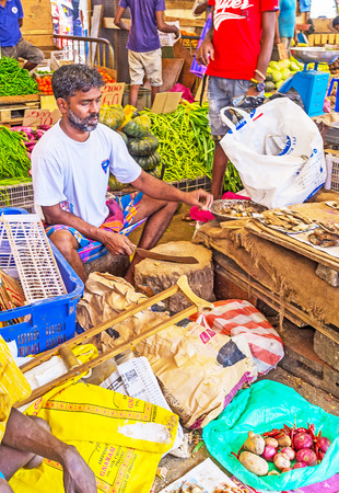 COLOMBO, SRI LANKA - DECEMBER 6, 2016: The seller of dried fish at Fose Market cuts it into smaller pieces, on December 6 in Colombo.