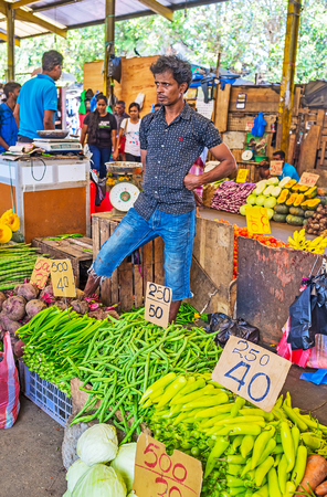 COLOMBO, SRI LANKA - DECEMBER 6, 2016: The Fose Market in Pettah with agricultural products, the seller in vegetable row offers green peppers, pea pods, okra (bamia) and red beetroots, on December 6 in Colombo.