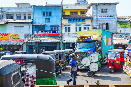 COLOMBO, SRI LANKA - DECEMBER 6, 2016: The street next to the Fose agricultural market is occupied with trucks, carried here fruits or vegetables and tuk tuks, serving as taxi or express delivery, on December 6 in Colombo.