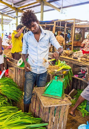 weighs: COLOMBO, SRI LANKA - DECEMBER 6, 2016: The seller weighs the leeks at the stall of Fose agricultural market, on December 6 in Colombo.