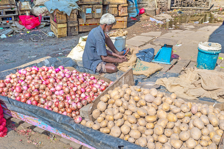 COLOMBO, SRI LANKA - DECEMBER 6, 2016: The slum market in Pettah, seller sits on the floor at large boxes with vegetables, on December 6 in Colombo.