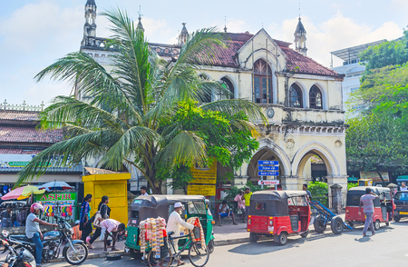 COLOMBO, SRI LANKA - DECEMBER 6, 2016: The facade of the old town hall, facing Gas Works Junction, crowded place with market stalls, street trade and traffic jams, on December 6 in Colombo.