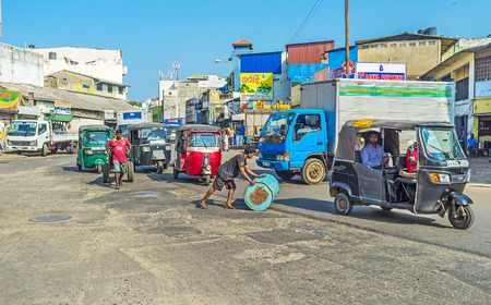 COLOMBO, SRI LANKA - DECEMBER 6, 2016: The porter rolls the barrel across the street with chaotic tuk tuk traffic, on December 6 in Colombo.