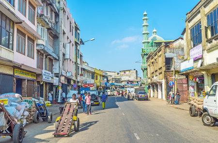 콜롬보, 스리랑카 -12 월 6 일, 2016 : Petta의 전 Wolfendhal 거리, 콜롬보에서 12 월 6 일 배경에 Jumma 모스크 (알 Masjid 알 Dheeniyah)의 녹색 미 나 렛 및 돔와 상점 및 창 고를 점령. 스톡 콘텐츠 - 73237142