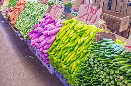 The colorful counter of the stall in Fose Market - dark green bamia, bright green pepper and beans, purple eggplant and orange carrot in separated heaps, Colombo, Sri Lanka. Banco de Imagens