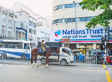 COLOMBO, SRI LANKA - DECEMBER 6, 2016: The mounted traffic policeman regulates the traffic on the Lotus road in Fort district, on December 6 in Colombo. Banco de Imagens - 73237170