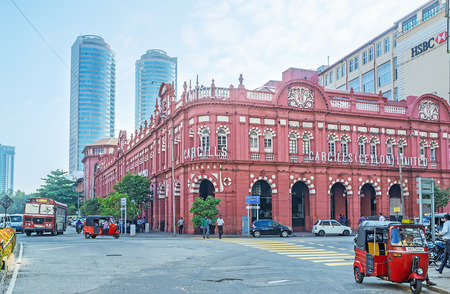 COLOMBO, SRI LANKA - DECEMBER 6, 2016: The red building of Cargills and Miller in York Street with the skyscrapers on the background, on December 6 in Colombo.