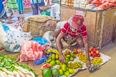 COLOMBO, SRI LANKA - DECEMBER 6, 2016: The aged seller arranges the small heaps of fruits on the floor in Fose Market in Pettah, on December 6 in Colombo.