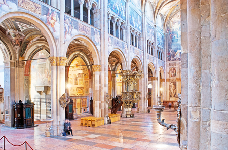 PARMA, ITALY - APRIL 24, 2012: The nave of Cathedral separated from the aisles with the stone pilasters and decorated with medieval frescoe and carved patterns, on April 24 in Parma.