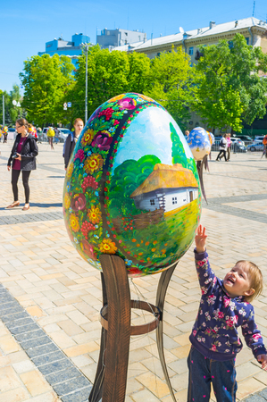 KIEV, UKRAINE - APRIL 29, 2016: The small happy kid reaches up to the giant Easter egg, on April 29 in Kiev