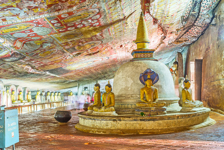 lena: DAMBULLA, SRI LANKA - NOVEMBER 27, 2016: The old Stupa in Maharaja Lena Cave (Great Kings) of Dambulla Temple Complex surrounded by numerous painted statues, on November 27 in Dambulla.
