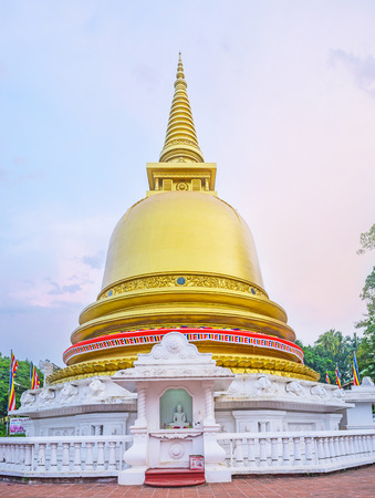 vihara: The gilt Pagoda of Dambulla Golden Temple with the statue of Meditating Lord Buddha at the altar, Sri Lanka.