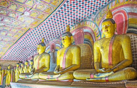 DAMBULLA, SRI LANKA - NOVEMBER 27, 2016: The row of staues of Buddha at the painted wall of Maha Alut Viharaya (Great New Temple) of Dambulla Cave Monastery, on November 27 in Dambulla.