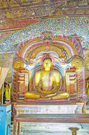 DAMBULLA, SRI LANKA - NOVEMBER 27, 2016: The statue of seated Lord Buddha, surrounded by carved Dragon Arch in Maha Alut Viharaya (Great New Temple) of Dambulla Cave Monastery, on November 27 in Dambulla. Editorial