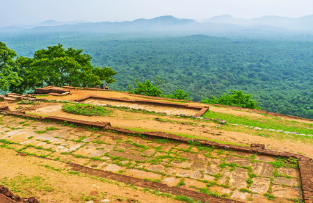 ancient lion: The foggy plain, covered with jungle forests, behind the ruins of upper palace, located on Sigiriya Rock summit, Sri Lanka.
