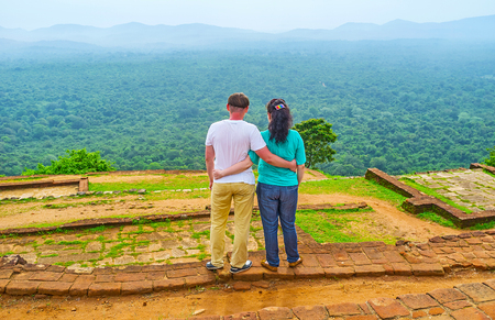 The couple enjoys the view from the top of Sigiriya Rock, hugging among the ruins of ancient upper palace, Sri Lanka.