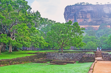 The footpath leads to Sigiriya Rock, the preserved ancient natural formation, that was used for building of citadel and preserves its ruins to nowadays, Sri Lanka. Banco de Imagens