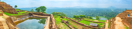 Panorama of the Upper Palace of Sigiriya with the cistern, full of water, ancient ruins and the green plain on the background, Sigiriya, Sri Lanka. Stock Photo