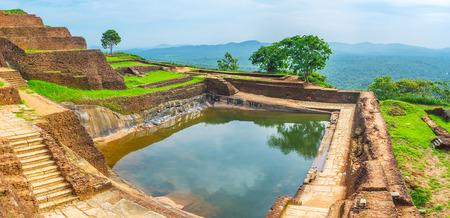 The water in cistern on Sigiriya Rock reflects the sky and trees, surrounding it, Sri Lanka.