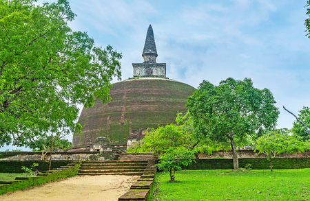 The path leads to the old brick Stupa of Rankoth Vihara, located in Polonnaruwa, Sri Lanka.