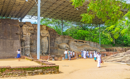 vihara: POLONNARUWA, SRI LANKA - NOVEMBER 27, 2016: The groups of tourists visit the Gal Viharaya or the Rock Temple, also famous as the Uttararama, known for the giant statues in granite rock, on November 27 in Polonnaruwa.