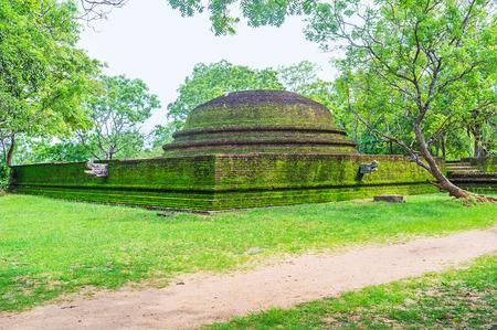 The brick stupa in Alahana Pirivena Complex covered with moss and surrounded by green trees, Polonnaruwa, Sri Lanka.