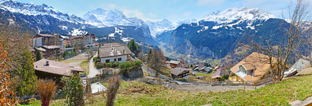 Panorama of the green mountain slope, covered with old wooden houses of Wengen resort and surrounded by snowy peaks of Alps, Switzerland. Stock Photo