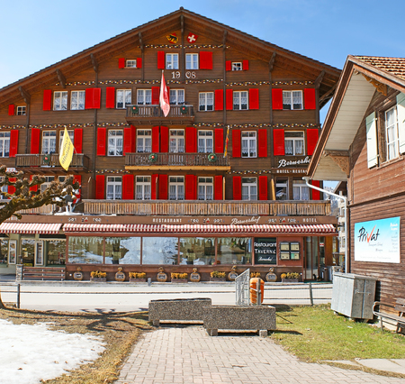 monch: WENGEN, SWITZERLAND - MARCH 22, 2011: The old wooden hotel and restaurant, decorated with bright red shutters and painted patterns, located in mountain resort, on March 22 in Wengen. Editorial