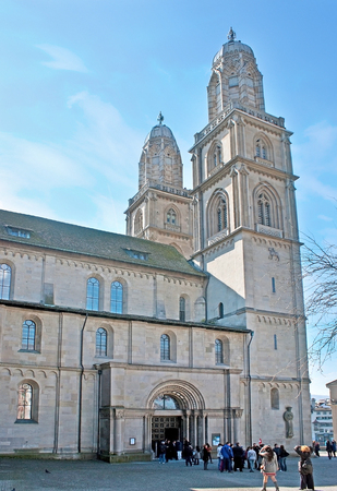 ZURICH, SWITZERLAND - MARCH 20, 2011: The tall belfries of Grossmunster Kirche (Great Minster) and the entrance to the church from Zwingliplatz square, on March 20 in Zurich.