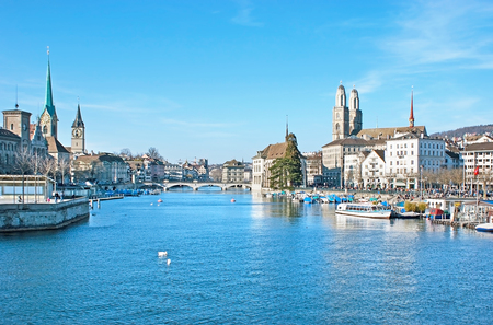 The banks of Limmat river occupied with the landmarks of Altstadt (Old Town) of Zurich - the medieval churches, stone bridges, palaces and mansions, Switzerland. Stock Photo