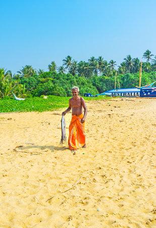 HIKKADUWA, SRI LANKA - DECEMBER 4, 2016: The smiling fisherman with the catched fish walks along the Dodanduwa harbor, on December 4 in Hikkaduwa.