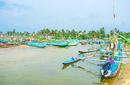 HIKKADUWA, SRI LANKA - DECEMBER 4, 2016: The colorful oruwa boats are moored in the place, where Ratgama Lake flows into the ocean, on December 4 in Hikkaduwa.