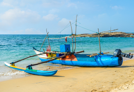 HIKKADUWA, SRI LANKA - 4 DE DICIEMBRE DE 2016: Los pescadores dirigen el barco a la orilla arenosa del puerto de Dodanduwa después de la pesca, el 4 de diciembre en Hikkaduwa.