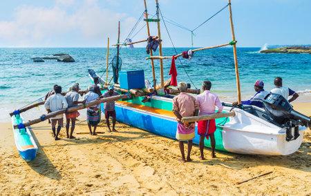 HIKKADUWA, SRI LANKA - DECEMBER 4, 2016: The fishermen hardly steer the heavy oruwa boat to the shore of Dodanduwa harbor, on December 4 in Hikkaduwa. Editorial