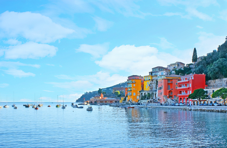The bright colored old houses in the center of Villefranche-sur-Mer, on the promenade of Darse harbor, France.