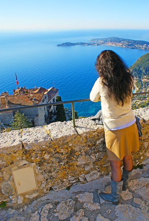 The girl watches the seascape from the viewpoint on the hilltop of Eze village, France.