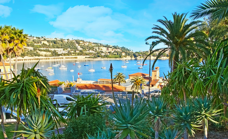 The lush garden with palm trees and yuccas opens the view on the Darse harbor of Villefranche-sur-Mer, France. Stock Photo