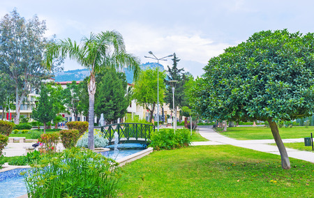 The scenic Olbia park with lush greenery, winding pond with fountains and tiny bridges, Kemer, Turkey. Zdjęcie Seryjne