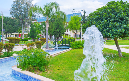 The Olbia park decorated with winding pond and fountains, surrounded by lush greenery, Kemer, Turkey.